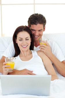 Lovers using a laptop on their bed
