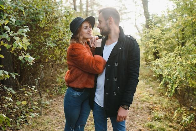 秋の公園で手をつないで歩く恋人たち