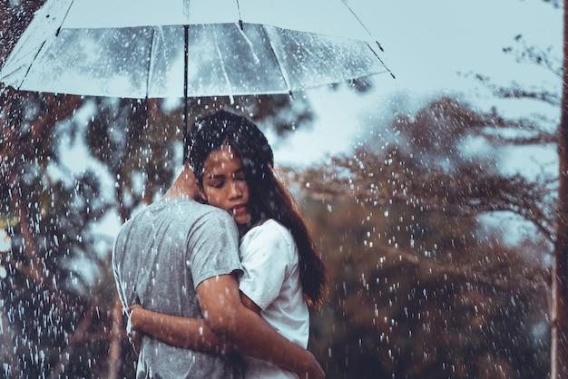 雨の下で傘を持つ恋人