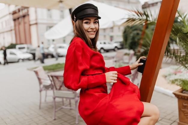 Lady lovey-dovey in abito rosso russo brillante ballando. foto di strada del giovane modello femminile dai capelli lisci