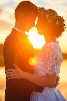 日没で一緒に立っている愛情のあるカップル。シルエット間の太陽光線。