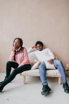 リラックスしたアフリカ系アメリカ人のカップルを愛する。家の内部で彼女の黒いボーイフレンドと一緒に暗い肌の少女。