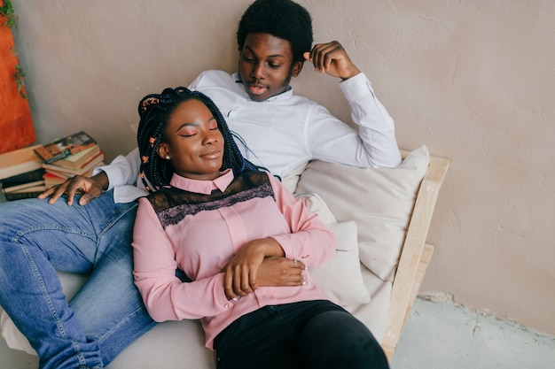 椅子でリラックスしたアフリカ系アメリカ人のカップルを愛する