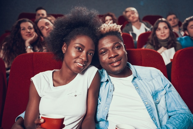 Loving african american couple watching movie in cinema.