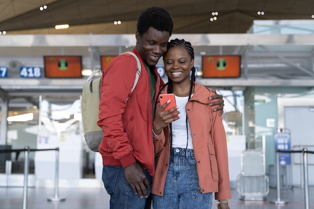 Loving african traveler couple waiting for flight in airport terminal looking at the phone