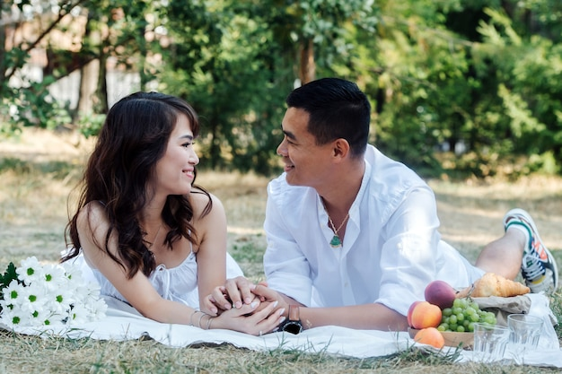 公園でピクニックをしている愛情のあるアジアのカップル、彼らの胃の上に横たわって、お互いを見ています。木の影で白い服を着て休んでいる男性と女性。