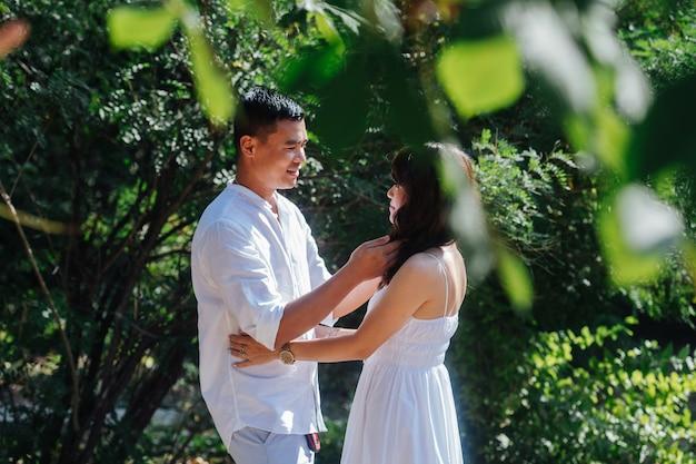 公園で時間を過ごす白い服を着た愛情のあるアジアのカップル。お互いを見て、お互いを抱きしめます。彼らは初秋の最後の暖かい日を楽しんでいます。