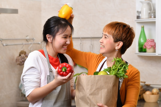 Loving asian family of mother and daughter cooking in kitchen making healthy food and holding grocery shopping bag with vegetables together feeling fun