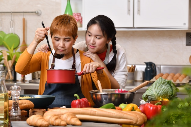Loving asian family of mother and daughter cooking in kitchen making healthy food together feeling fun