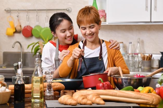 건강한 음식을 함께 만드는 재미를 느끼는 부엌에서 요리하는 어머니와 딸의 사랑하는 아시아 가족
