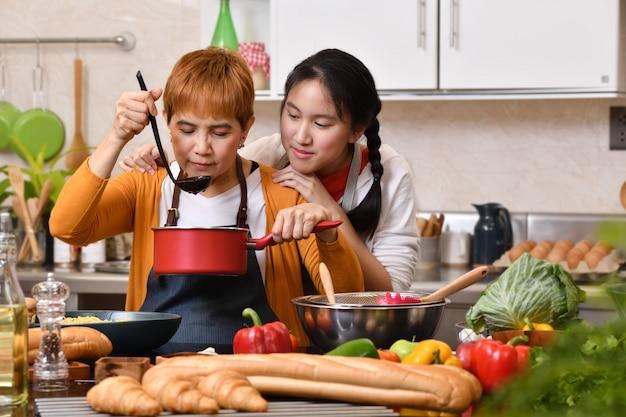 Любящая азиатская семья матери и дочери готовит еду на кухне