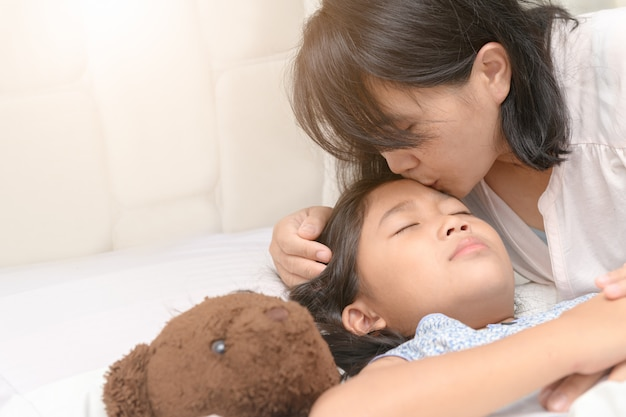 Loving asian mother gently kissing cute kid daughter wishing good night