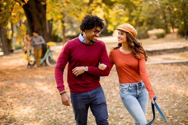 Влюбленная красивая пара афро-американский мужчина и кавказская женщина гуляют в осеннем парке