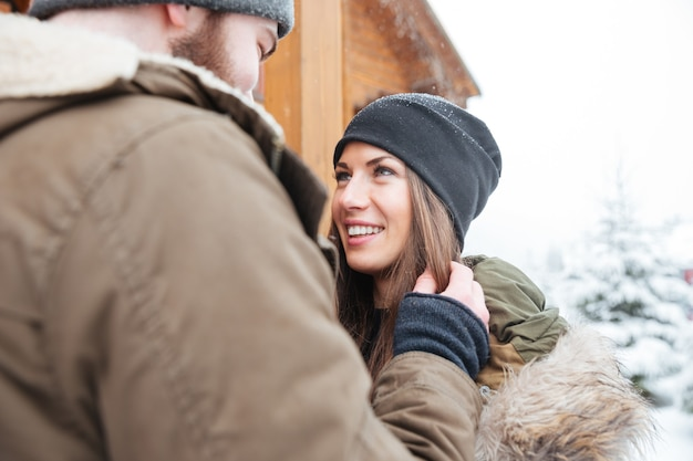 Loving beautiful couple standing outdoors together in winter