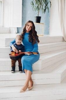 Любящая красивая мама играет на музыкальном инструменте с сыном