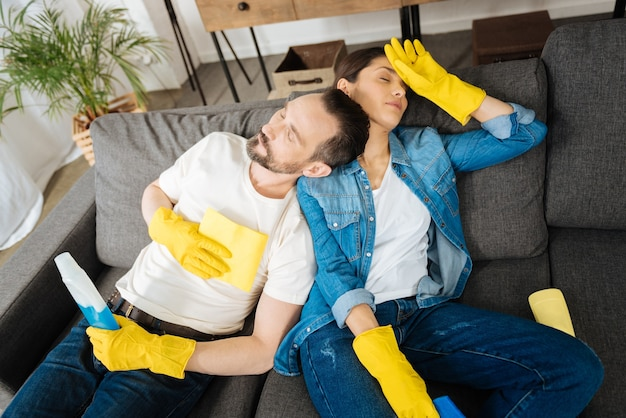 Loving beautiful young couple closing eyes while dressing in gloves and sleeping on the couch