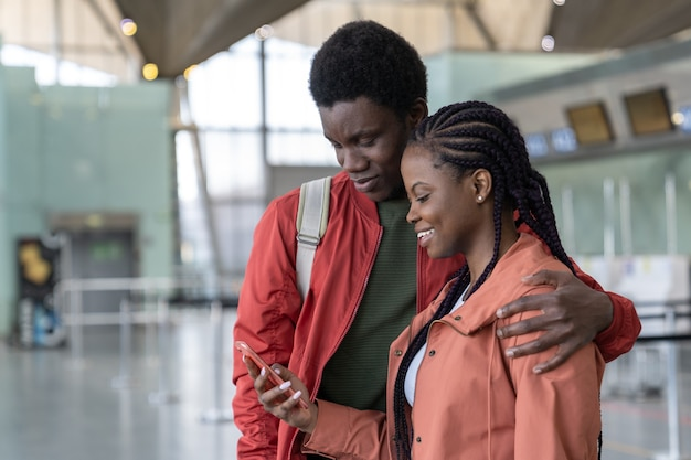 Loving black traveler couple waiting for flight in the airport terminal looking at the phone