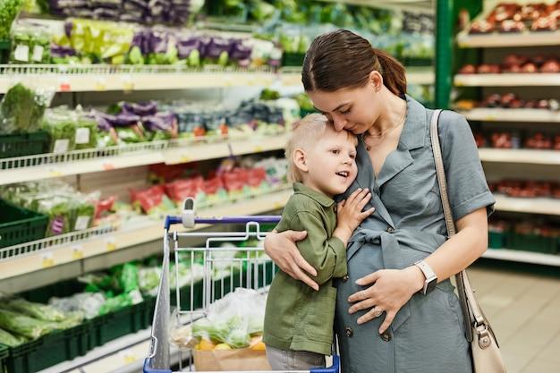 Loving boy cuddling pregnant mother in store