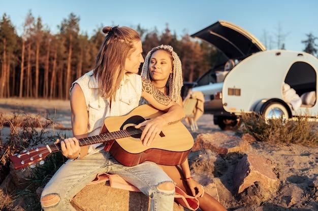 愛する彼氏。ドレッドヘアを持つ彼の魅力的な女性のための長いブロンドの髪の歌の歌を持つ愛情のあるボーイフレンド