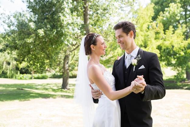Loving bride and groom dancing in garden