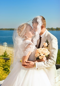 Loving bride and groom sheltered veil bride embrace on the river bank