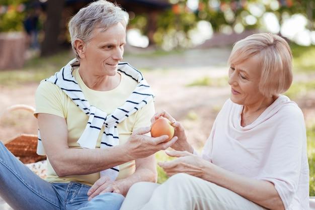 Loving caring aged couple expressing joy while enjoying picnic and eating fruits
