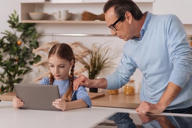ケアを表現し、小さな孫娘からタブレットを奪いながら家に立っている思いやりのある老化した祖父を愛する