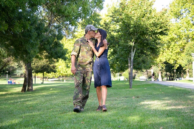 Loving caucasian couple embracing, kissing and walking together on lawn in park. middle-aged soldier in military uniform, hugging his pretty wife. family reunion, weekend and returning home concept