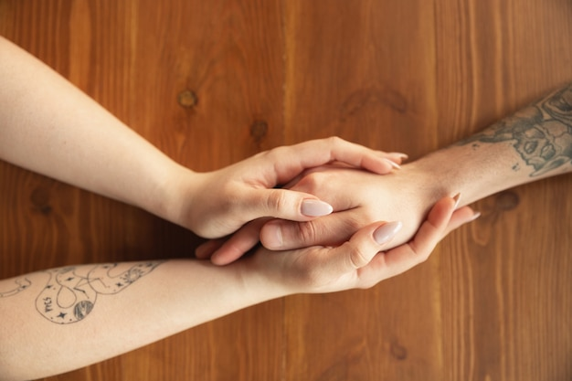 Loving caucasian couple holding hands close-up on wooden wall.