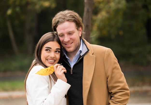 Amorevole coppia caucasica che cammina nel parco in autunno