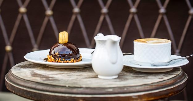 愛するコーヒー。新鮮なカプチーノのカップ。チョコケーキ。閉じる。おいしいチョコレートケーキ。カップに入ったカプチーノ、ホットラテ、美味しいコーヒー。コーヒータイム。朝のカフェでのコーヒーまたはコーヒーカップ。