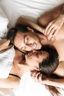 Loving couple 30s hugging together, while lying in bed at home or hotel apartment