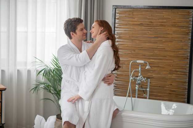 愛するカップル。抱きしめ、愛情を感じる白いバスローブを着た男と女