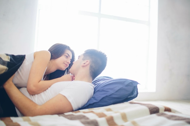 A loving couple are lying on the bed. bright and cozy bedroom