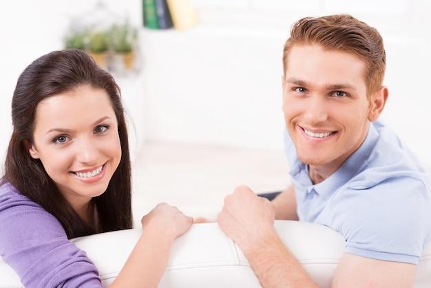 집에서 사랑하는 부부. 아름다운 젊은 부부가 소파에 함께 앉아 미소를 지으며 카메라를 바라보는 모습