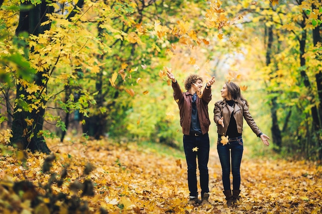 Loving couple in an autumn park man and woman cheerfully throw yellow leaves up