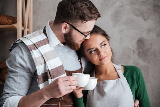 Loving couple bakers drinking coffee