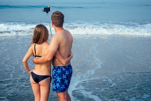 A loving couple on the beach is photographed with a self-stick.