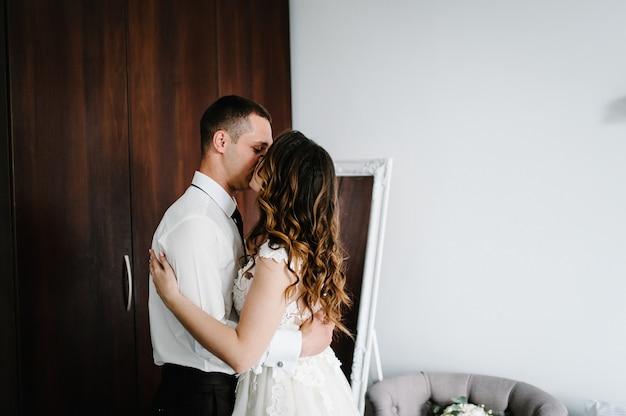 Влюбленная пара, жених и невеста обнимаются и целуются в помещении. свадебное утро.