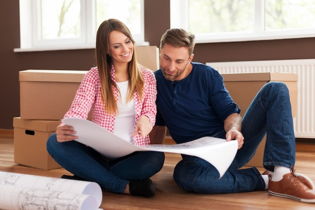 Loving couple checking blueprints of new home