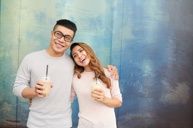 Loving couple cheerfullly smiling holding milkshakes