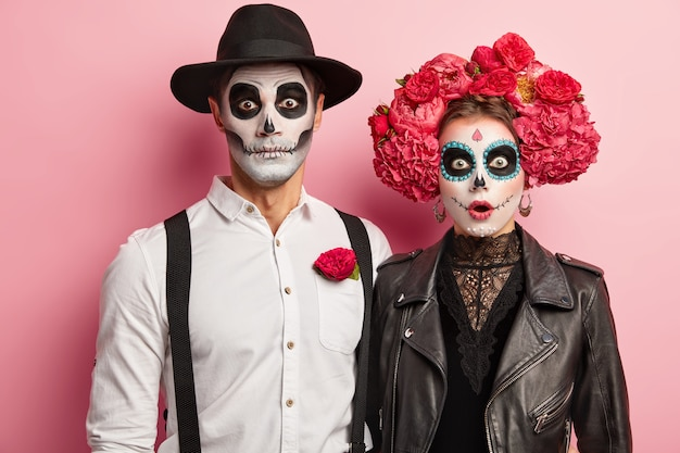 Loving couple in costumes of skeletons and skull makeup, have scared expressions, celebrate autumn holiday, pose during horror party, isolated over pink background. happy halloween time concept