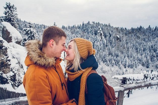 重い冬のコートと毛皮のボンネットを身に着けている雪の風景の中で屋外に寄り添う愛情のあるカップル。