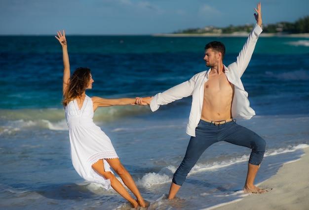크리스탈 푸른 물에 대 한 여름에 바다 해변에서 모래에서 춤을 사랑하는 부부 프리미엄 사진