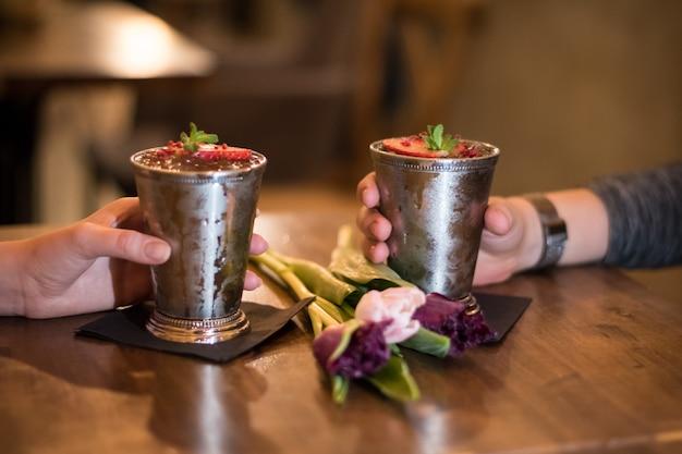 Coppia di innamorati bere cocktail con tazze di metallo e tulipani sul tavolo
