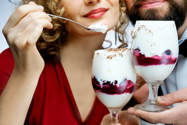 Loving couple eating cherry ice cream together. man in the bow tie girl in a red dress on a white background