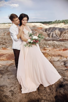 Loving couple embraces in red mountains. love