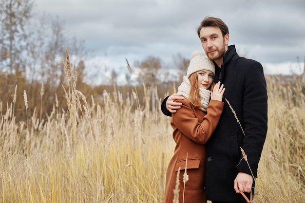 Loving couple embracing in field, autumn landscape