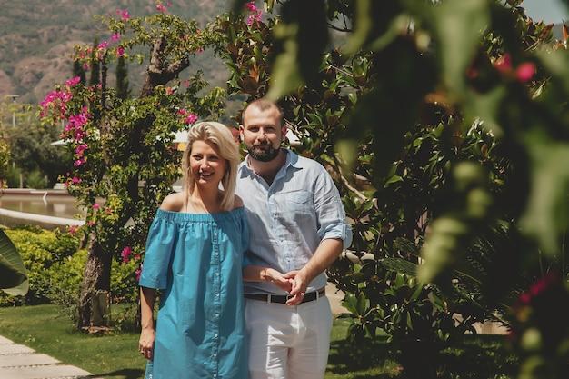 럭셔리 호텔에서 신혼여행을 즐기는 사랑하는 커플, 야자수와 아름다운 꽃이 있는 부지를 걷는다