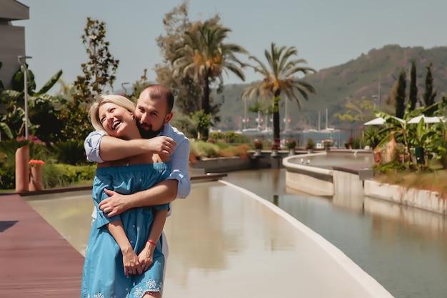 고급 호텔에서 신혼여행을 즐기는 사랑하는 커플, 야자수와 수영장이 있는 부지를 걷는다